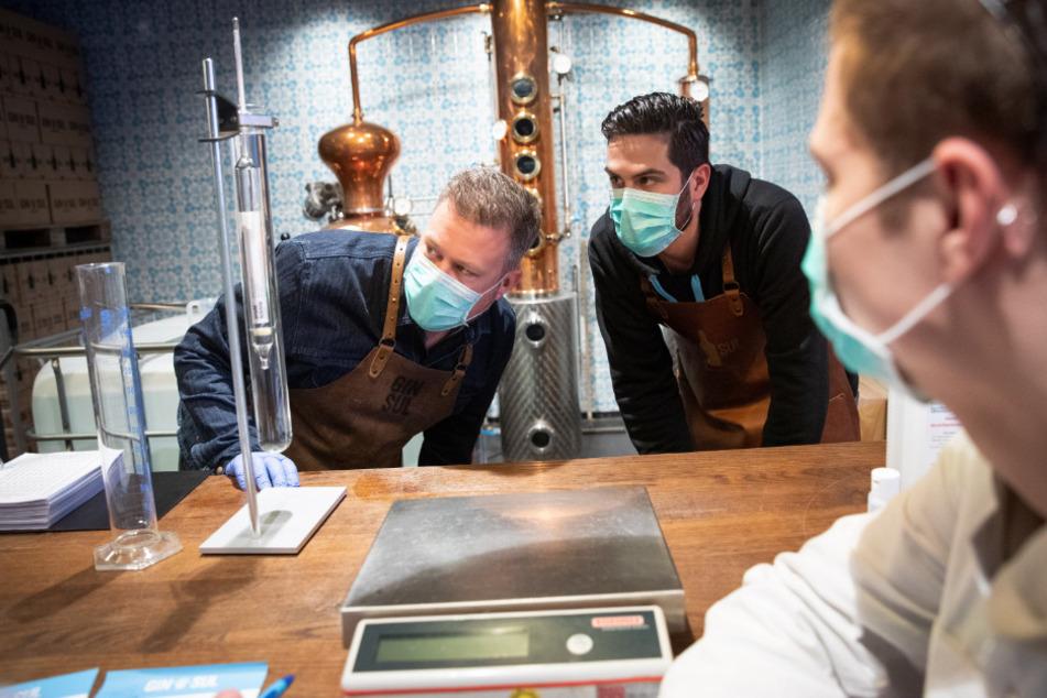 Stephan Garbe (l), Rafael Viera (M), und Lasse Gnekow prüfen den Alkoholgehalt beim mischen eines Desinfektionsmittels.