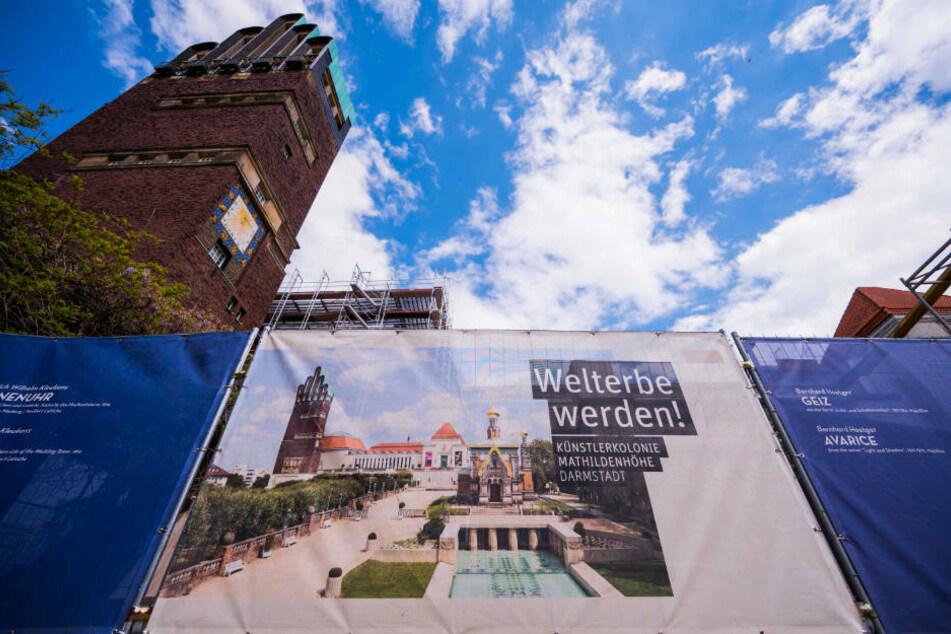 """Ein Plakat informiert über die Bewerbung der Mathildenhöhe um den Status """"Unesco-Welterbe""""."""