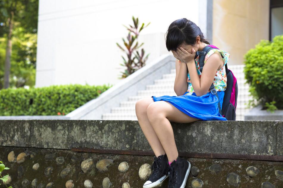 Eine Schülerin sitzt auf einer Mauer. (Symbolbild)