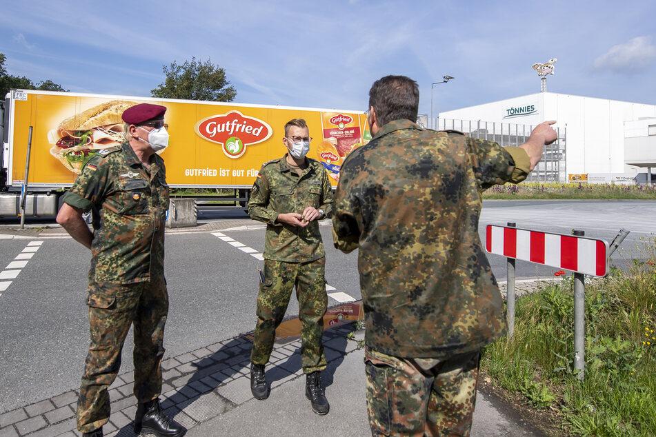 Soldaten der Bundeswehr stehen an der Einfahrt für LKW-Fahrer zum Betriebsgelände der Fleischfabrik Tönnies.