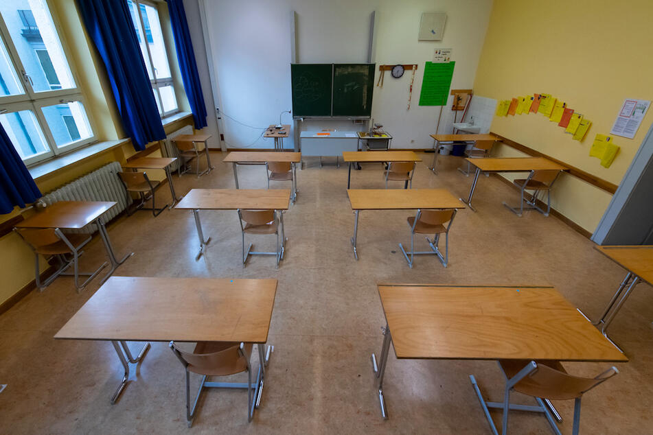 Die Tische sind in einem Klassenzimmer mit dem vorgeschriebenen Mindestabstand aufgestellt.