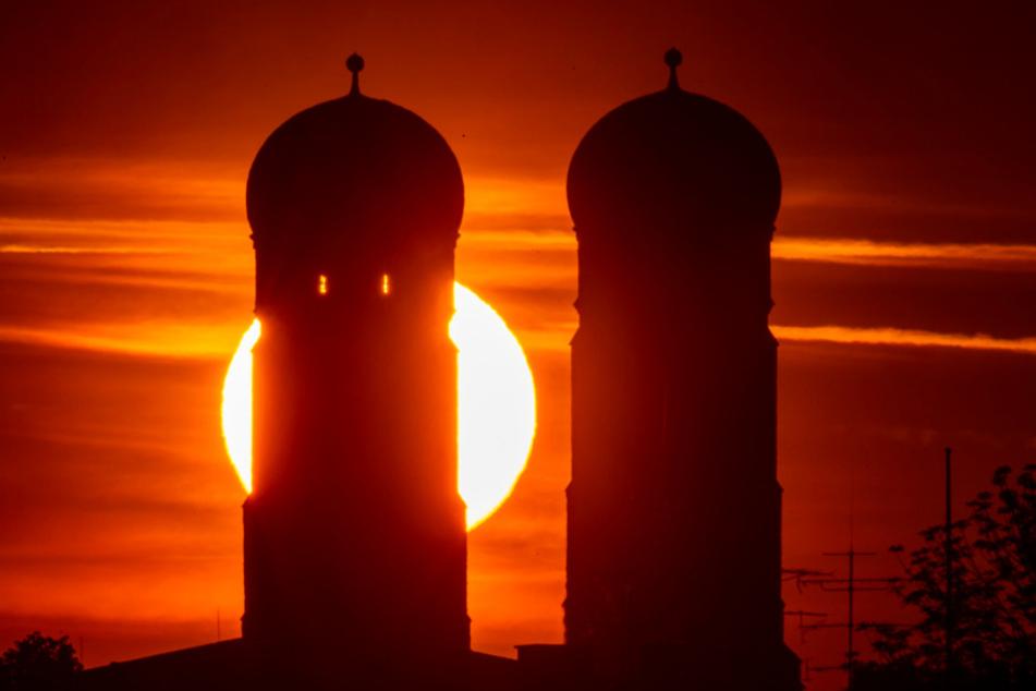 Die Sonne geht am frühen Morgen zwischen den Türme der Frauenkirche auf, die im Herzen der bayerischen Landeshauptstadt steht.