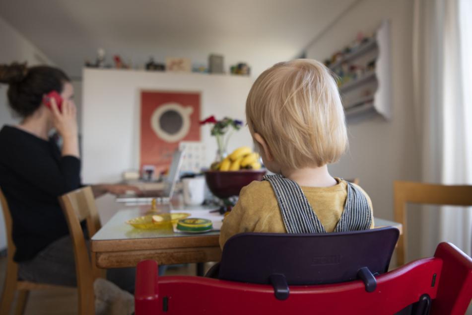 Eine Frau arbeitet im Home Office, während ihr Kind daneben sitzt.