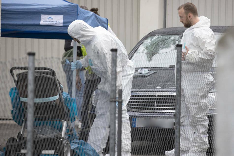 Kriminalbeamte der hessischen Polizei untersuchen den Tatort im Stadtteil Griesheim nach Spuren.