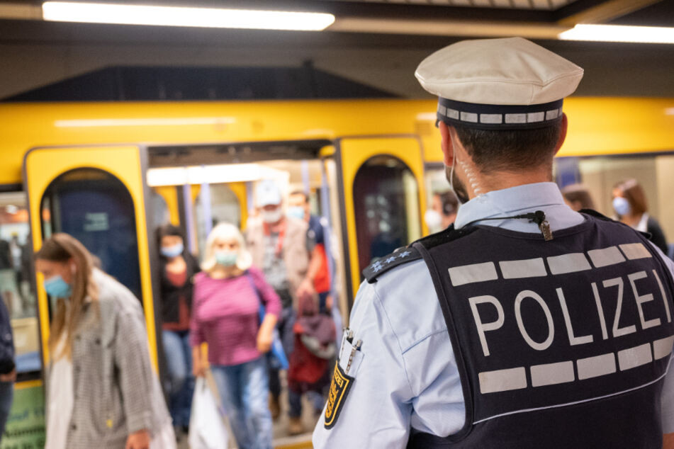 Ein Polizeibeamter kontrolliert an einer Haltestation die Einhaltung der Maskenpflicht.