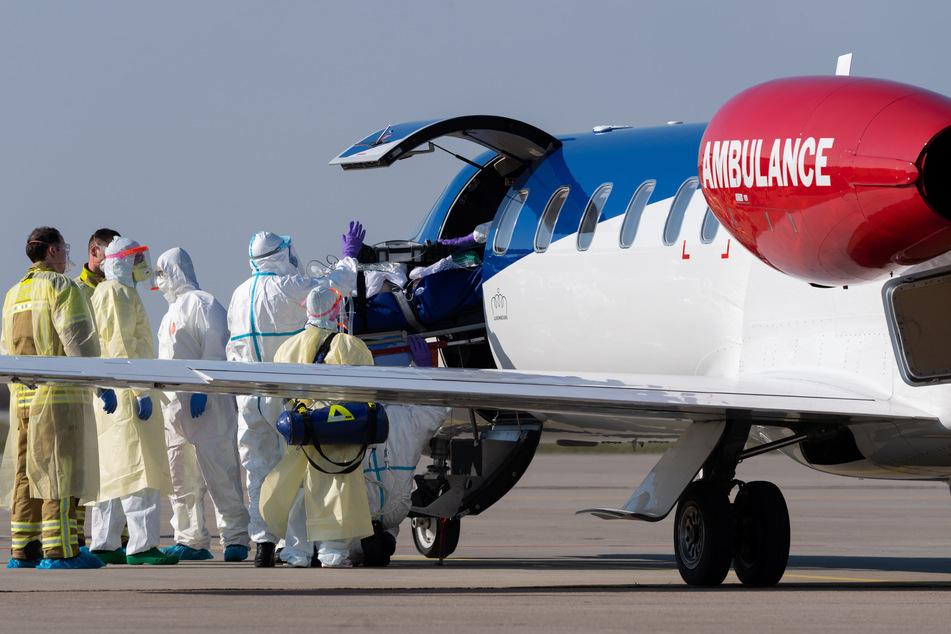 Ein schwer kranker Covid-19-Patient aus Frankreich wird auf dem Flughafen Dresden International aus einem Ambulanzflugzeug in den Krankenwagen transportiert.