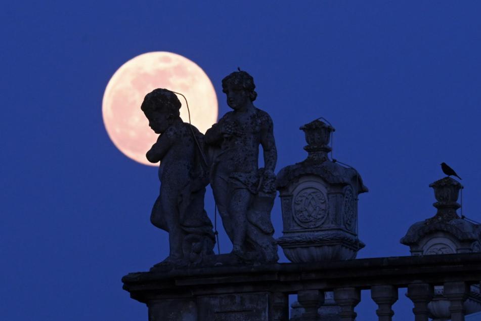 Der Mond hinter Statuen und Amphoren auf dem Dach der Orangerie in Kassel.