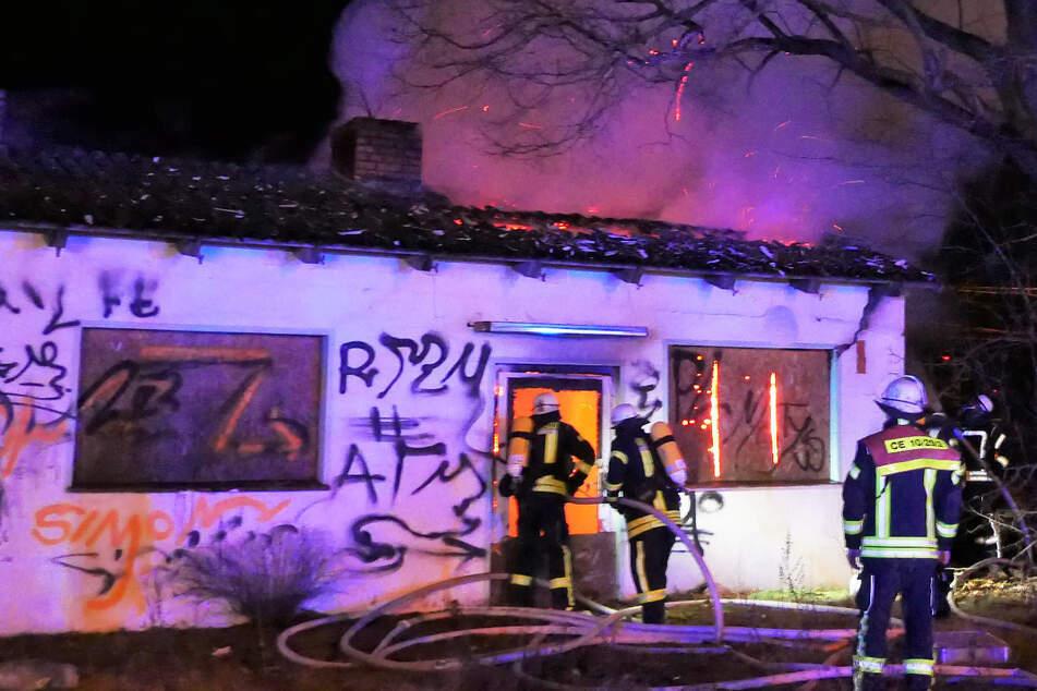 Einsatzkräfte stehen vor dem brennenden Gebäude.