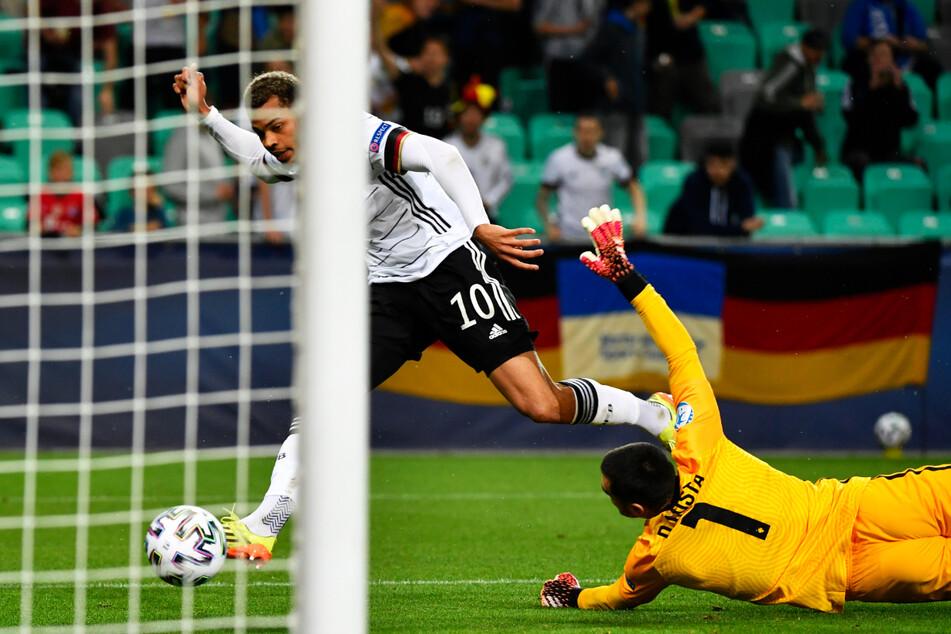 Klasse Aktion! Lukas Nmecha (l.) legt den Ball an Diogo Costa vorbei und schiebt zur 1:0-Führung für die DFB-Elf ein.