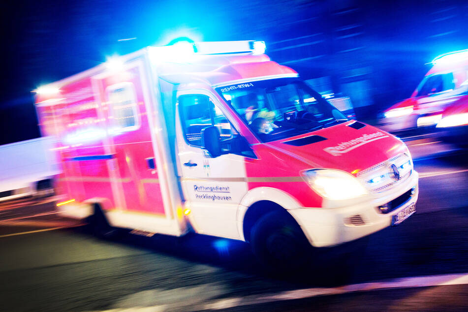 Ein Rettungswagen der Feuerwehr fährt mit Blaulicht durch eine Straße. (Symbolbild)