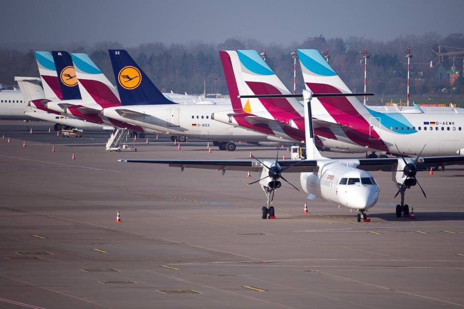 Flugzeuge von Lufthansa und Eurowings stehen auf dem Vorfeld des Flughafen in Düsseldorf.