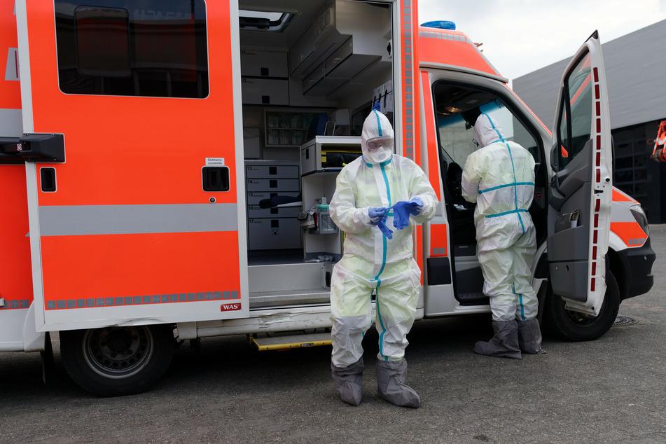 Mitarbeiter der Rettungsdienste schützen sich mit Anzügen und Masken vor einer Vireninfektion.