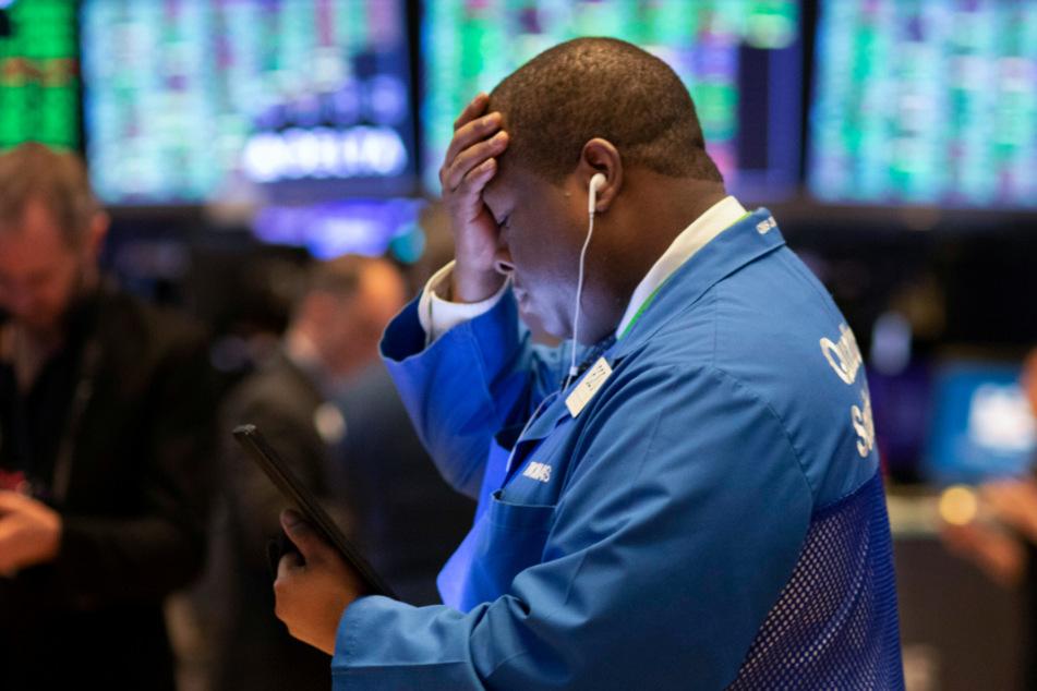 Der Börsenhändler Thomas Lee arbeitet an der Wertpapierbörse New York Stock Exchange. Der Crash am US-Aktienmarkt hat sich am Freitag zunächst nicht fortgesetzt.
