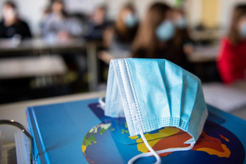 Ein Mund- und Nasentschutz liegt im Unterricht einer Gymnasium-Schulklasse.