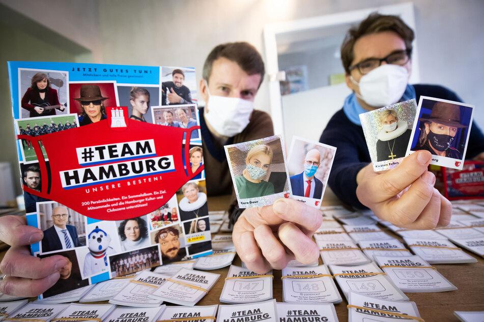 Alexander Böker (l) und Oliver Wurm halten das von ihnen herausgegebene Panini-Sammelalbum in die Kamera.