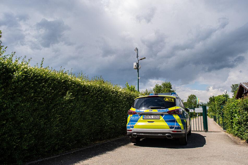 Ein Polizeiauto steht vor der Gartenanlage, in der der vermutliche Haupttäter Teile seiner Server-Anlage in einer Gartenlaube unterbrachte.