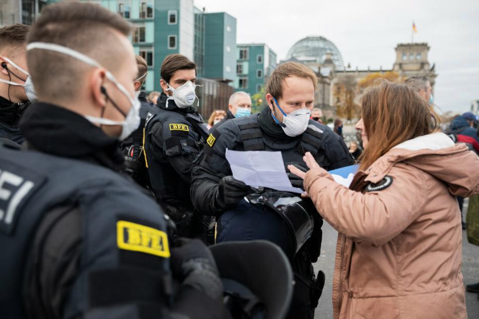 Polizisten kontrollieren bei einer Demonstration das Attest einer Frau zur Befreiung von der Maskenpflicht. Wegen falscher Corona-Atteste ermittelt das Landeskriminalamt in der Hauptstadt in dutzenden Fällen gegen Ärzte.