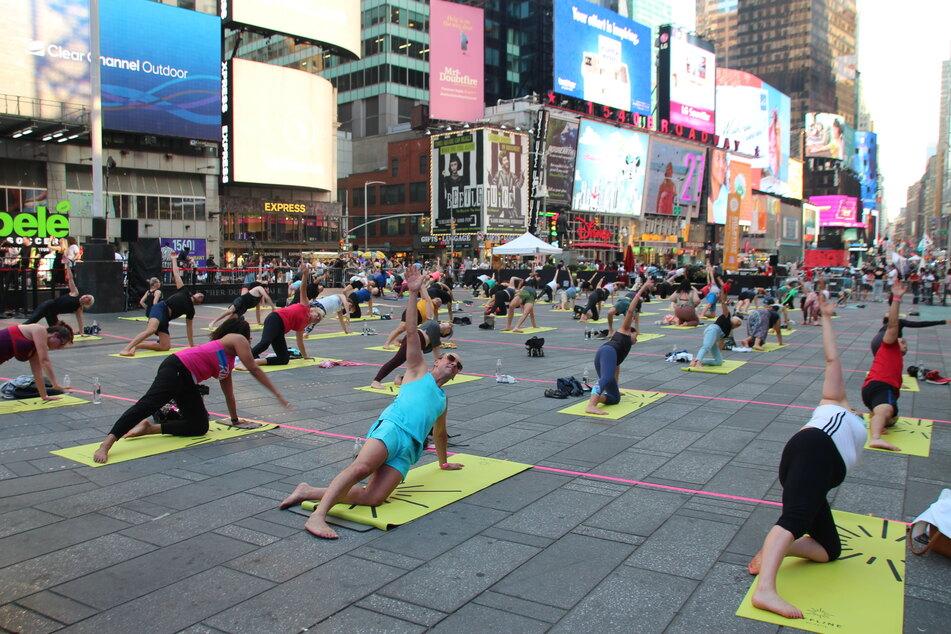 Menschen nehmen an einer gemeinsamen Yoga-Stunde inmitten des Times Square in New York teil.