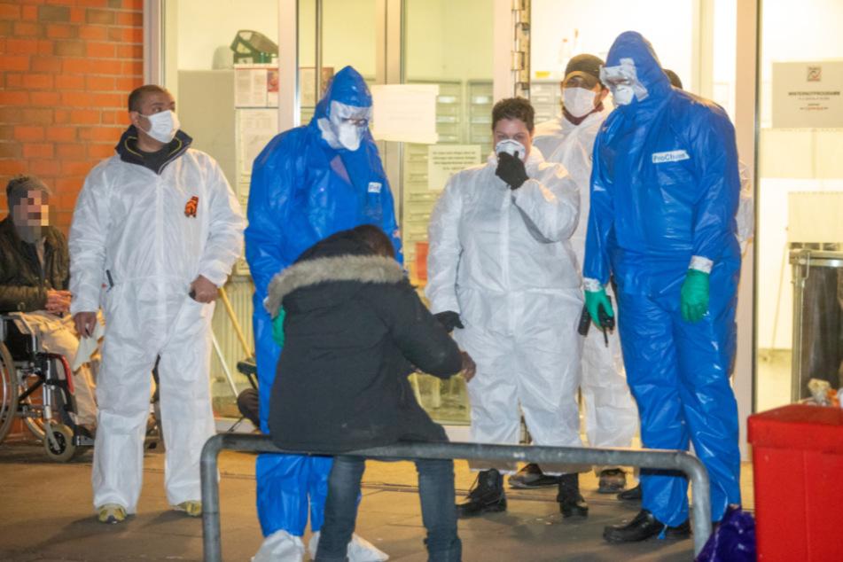 Beamte in Schutzanzügen stehen vor der Notunterkunft in der Friesenstraße.