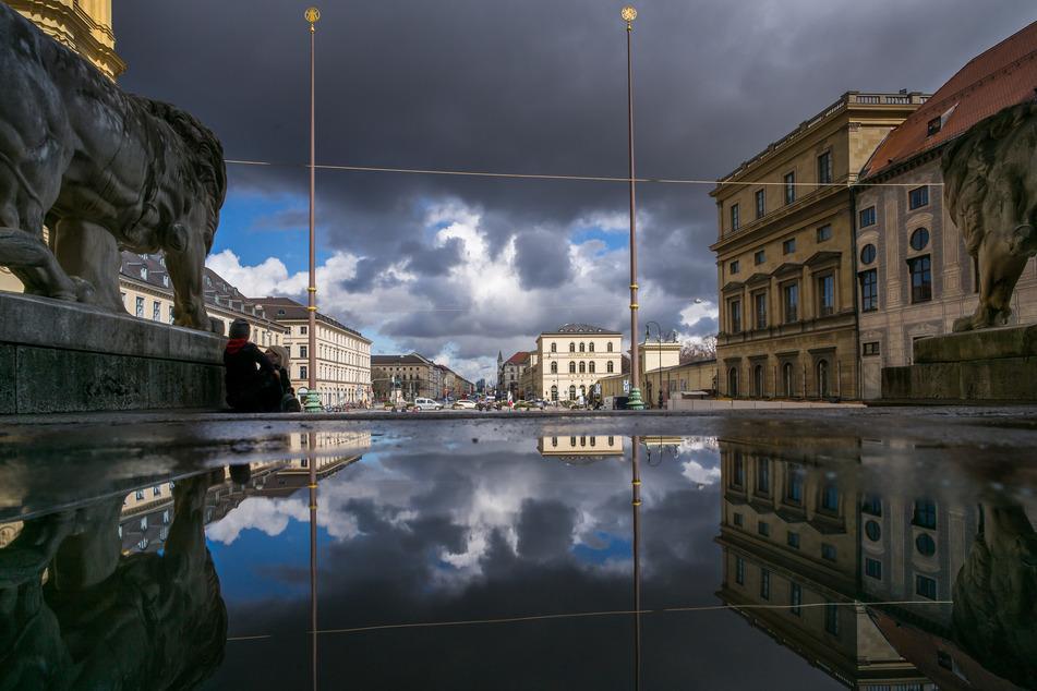 Wolken spiegeln sich in einer Pfütze in der Feldherrnhalle in Richtung Ludwigstraße, deren Bauten von der Sonne beschienen werden. (Archivbild)