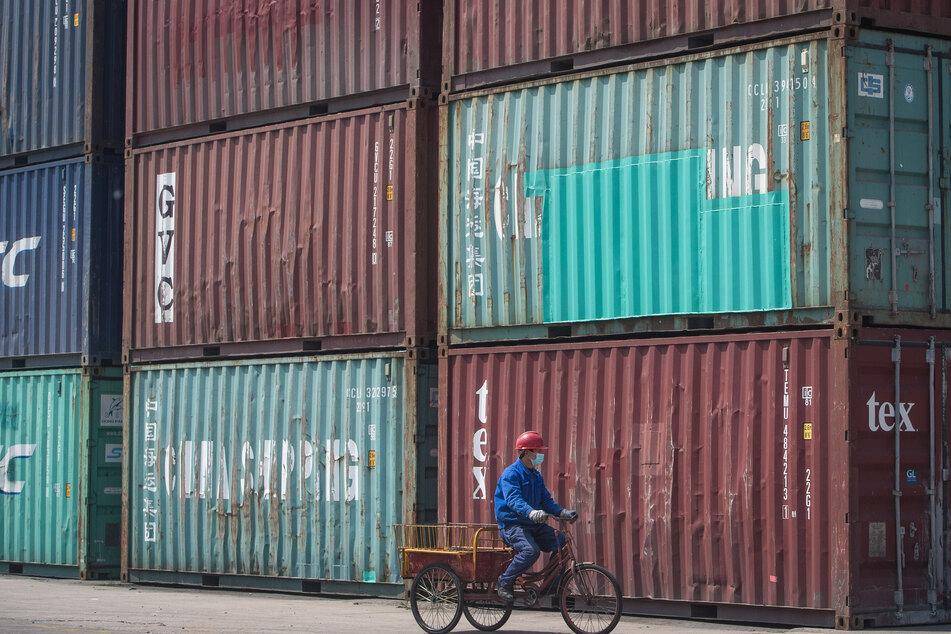 in Mitarbeiter fährt im Hafen Yangluo in Wuhan mit einem Lastenrad an Containern vorbei. Mehr als zweieinhalb Monate nach der Abriegelung von Wuhan werden die Beschränkungen in der Millionenmetropole langsam wieder aufgehoben.