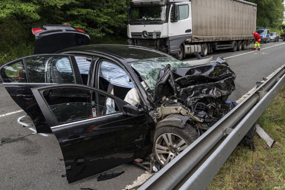 Ein zestörter PKW steht an einer Leitplanke, vor einem beschädigten Lkw.