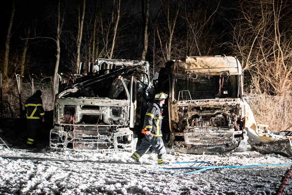Ein Feuerwehrmann geht an den Wracks der beiden ausgebrannter Lastwagen vorbei.