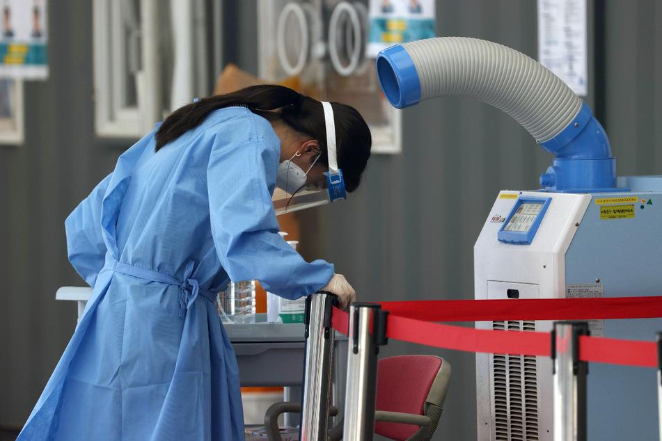 Seoul: Eine medizinische Mitarbeiterin einer Corona-Teststation steht vor einem Luftkühler inmitten sengender Hitze.