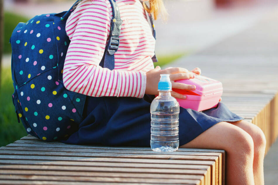 Ein Schulmädchen öffnet seine Lunchbox (Symbolbild).
