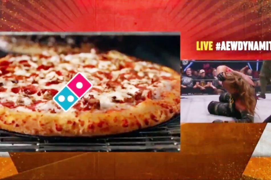 Dominos wirbt in Live-TV-Übertragung, während sich Jericho seine blutende Stirn halten muss.