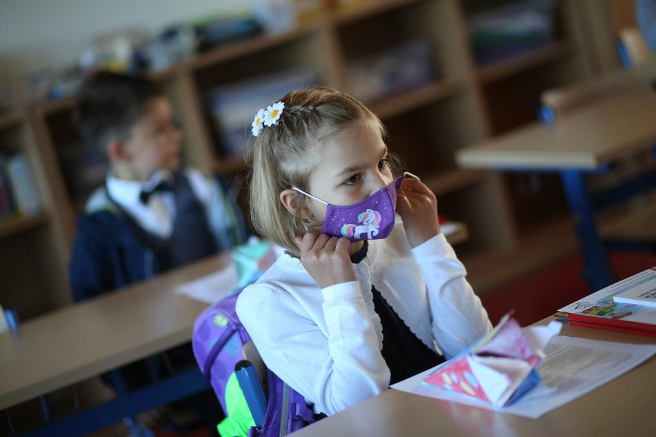 Eine Schülerin sitzt mit Mund-Nasenschutz in ihrem Klassenraum. (Symbolbild)