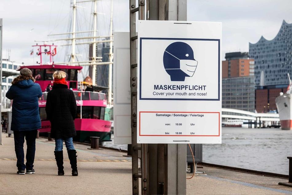 """Ein Hinweisschild mit der Aufschrift """"Maskenpflicht"""" hängt an den Landungsbrücken."""