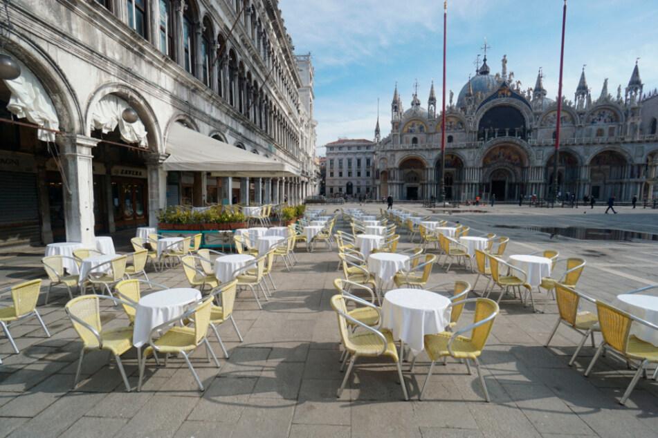 Venedig: Leere Stühle und Tische stehen vor einem Restaurant auf dem Markusplatz. Italien hat die höchste Zahl an nachgewiesenen Covid-19-Toten nach China. Die Sperr-Maßnahmen gelten nun für das ganze Land.