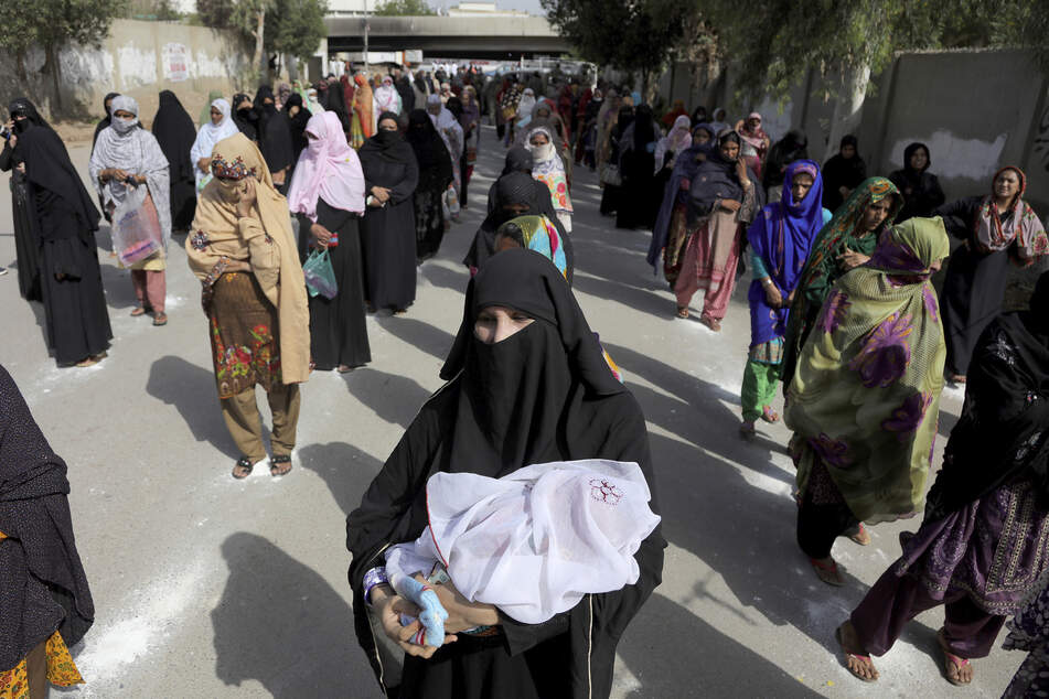 Pakistan: Frauen warten mit Abstand in auf den Boden gemalten Markierungen um Bargeld im Rahmen eines staatlichen Notfallprogramms für bedürftige Familien zu erhalten. (Archivbild)
