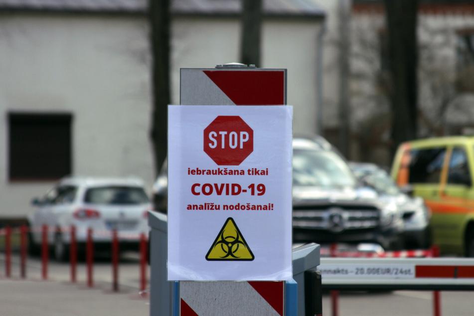 """Ein Schild mit einem Stoppzeichen und der Aufschrift """"Iebrauksana tikai Covid-19 Analizu nodosanai"""" (Einfahrt nur zur Abgabe von Covid-19 Analyse) hängt an einer Schrankenanlagen an der Einfahrt zur Teststation an der Pauls-Stradins-Universitätsklinik in Riga."""