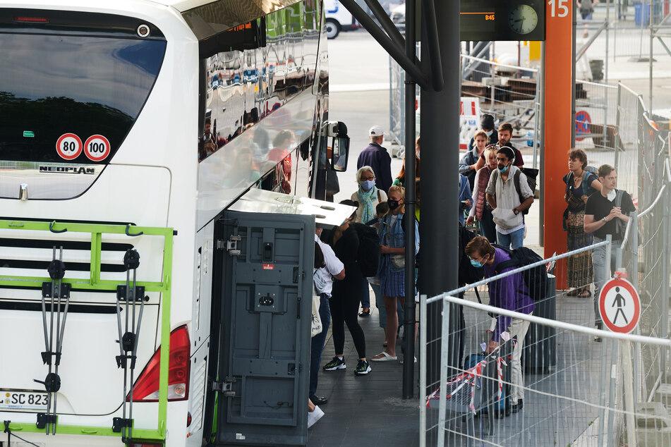 Reisende kommen mit einem Bus am Berliner ZOB an.