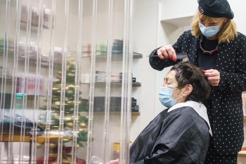Eine Friseurin in Frankfurt arbeitet im Dezember 2020 am Haarschopf einer Kundin.