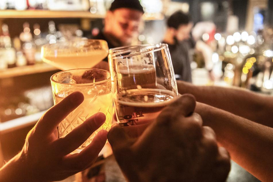 Gäste prosten sich in einer Bar zu. (Symbolbild)