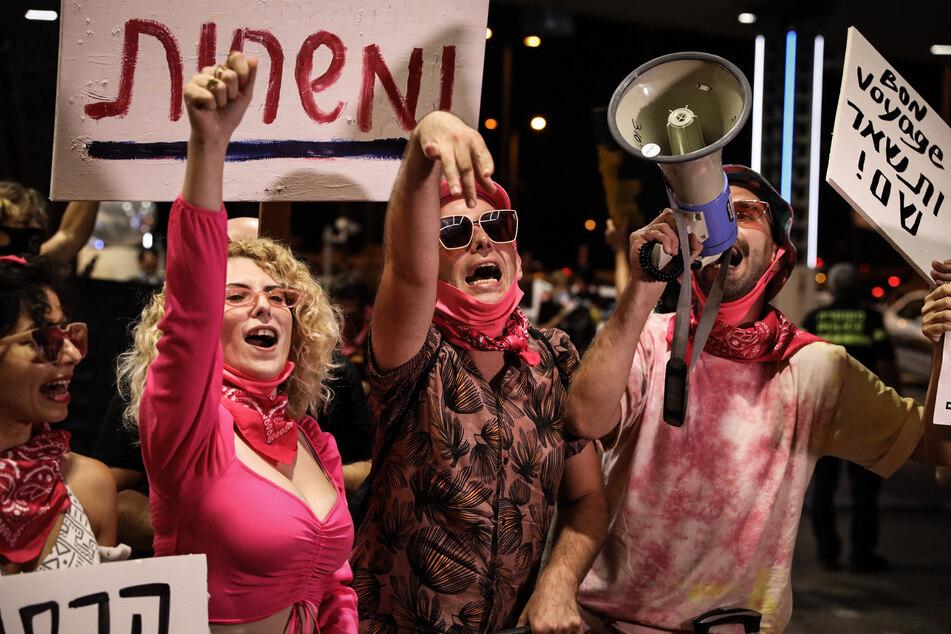 Demonstranten und Demonstrantinnen rufen Parolen in ein Megafon bei einem regierungskritischen Protest vor dem Flughafen Ben Gurion vor dem Abflug des israelischen Premierministers Netanjahu in die USA. Israels Regierung hat angesichts steigender Neuinfektionen mit dem Corona-Virus die Verhängung eines zweiten landesweiten Lockdowns beschlossen.