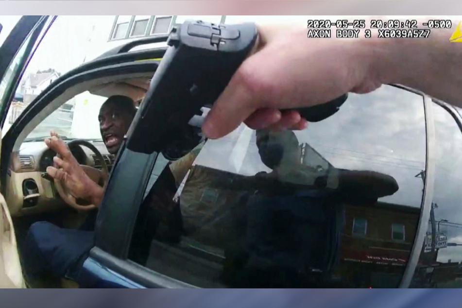 Das Standbild einer Aufnahme von der Körperkamera eines Polizisten zeigt, wie George Floyd (l) am 25. Mai 2020 vor einem Restaurant in seinem Auto sitzt, und eine Waffe auf ihn gerichtet ist.
