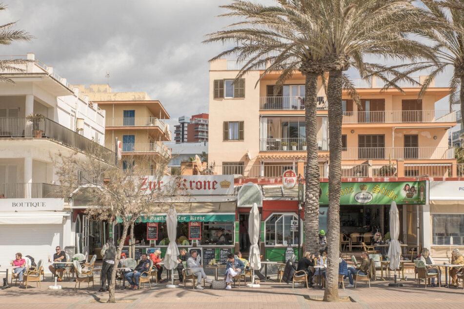 Deutsche Touristen sitzen in der bekannten Bar Zur Krone & Krone Stube und genießen einen Drink in der Sonne an der Playa de Palma auf Mallorca.