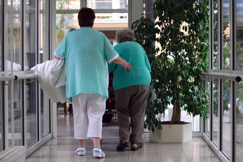 Eine Altenpflegerin geht mit einer Seniorin durch einen Flur in einem Altenheim. (Archivbild)