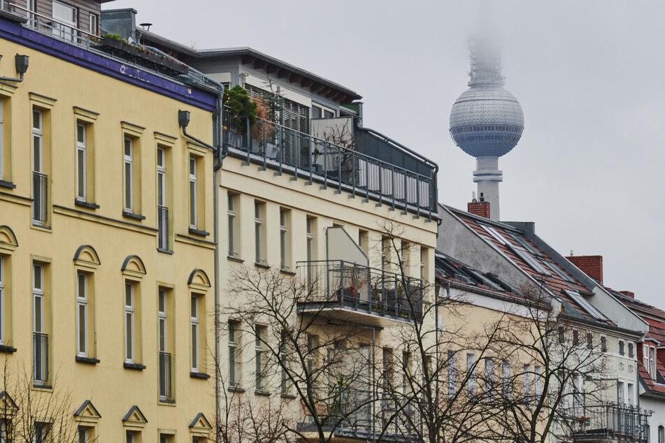 Der Fernsehturm verschwindet hinter einer Häuserreihe im Stadtteil Prenzlauer Berg im Nebel.
