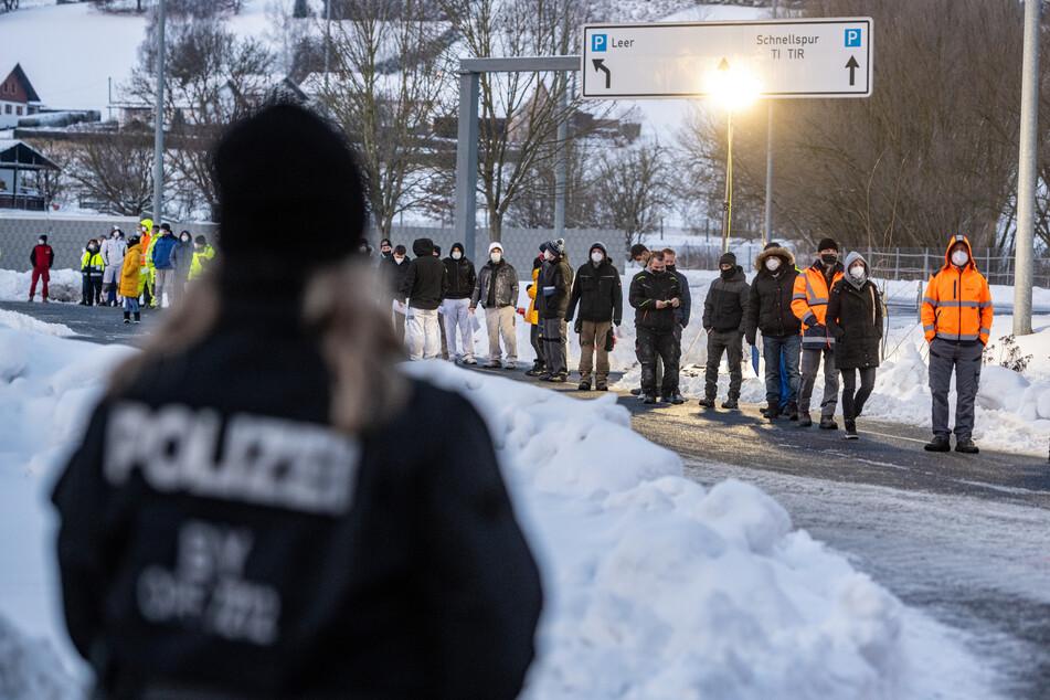 Mehrere Menschen stehen an der Grenze zu Tschechien.