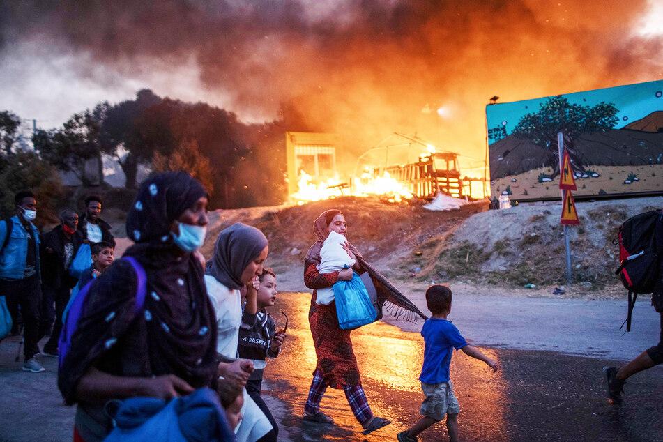 Migranten fliehen vor einem Feuer mit ihren Habseligkeiten aus dem Flüchtlingslager Moria.