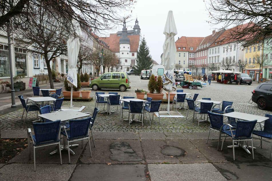 Leere Tische und Stühle stehen vor Cafes am Marktplatz der Stadt Hildburghausen.