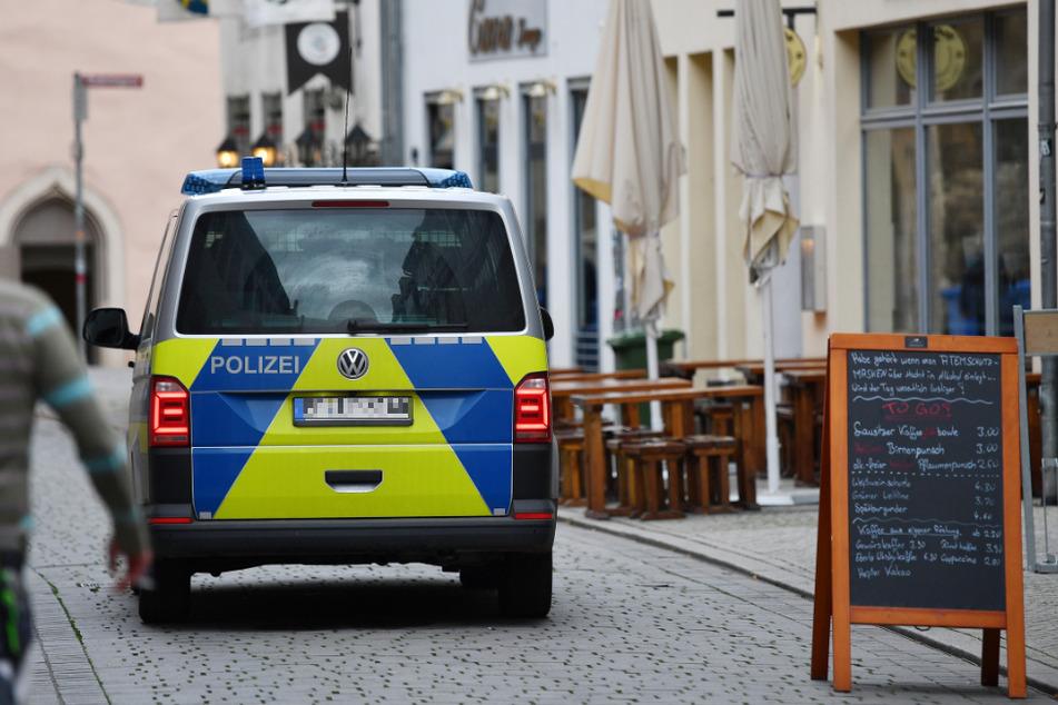Ein Polizeifahrzeug fährt an geschlossenen Restaurants in der Michaelisstraße in Erfurt vorbei. Mit Schließungen im Gastronomiebereich sollen die steigenden Infektionszahlen wieder fallen.