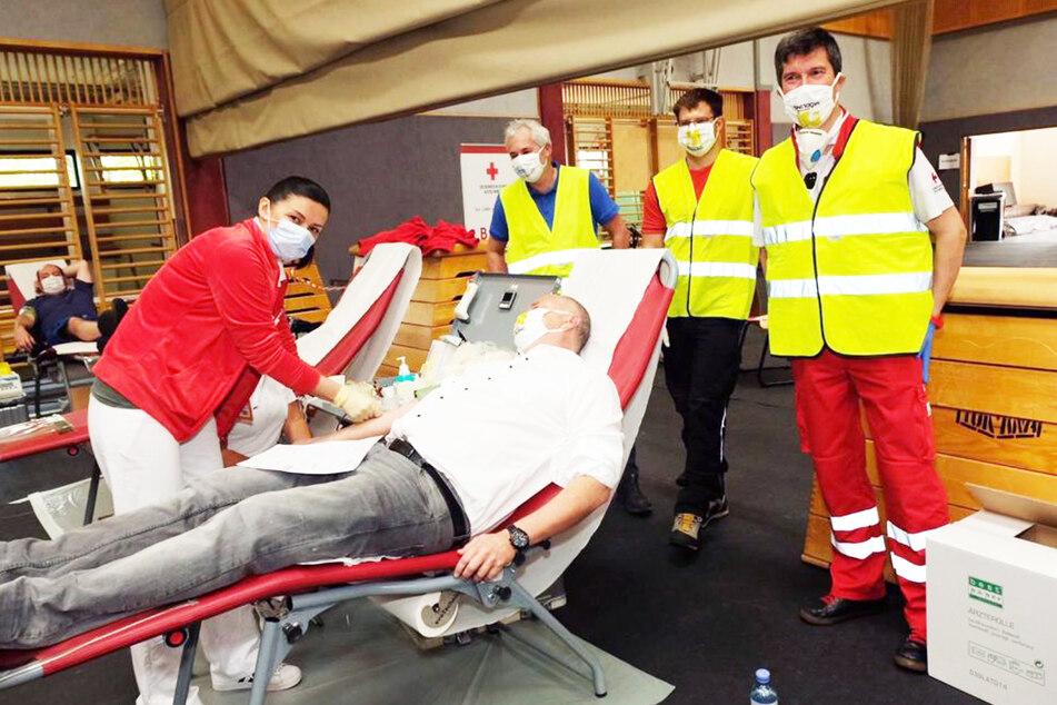 Eine Mitarbeiterin des Blutspendedienstes nimmt einem Spender Blut ab, während die Helfer von Feuerwehr, Bergrettung und Rotem Kreuz zuschauen.