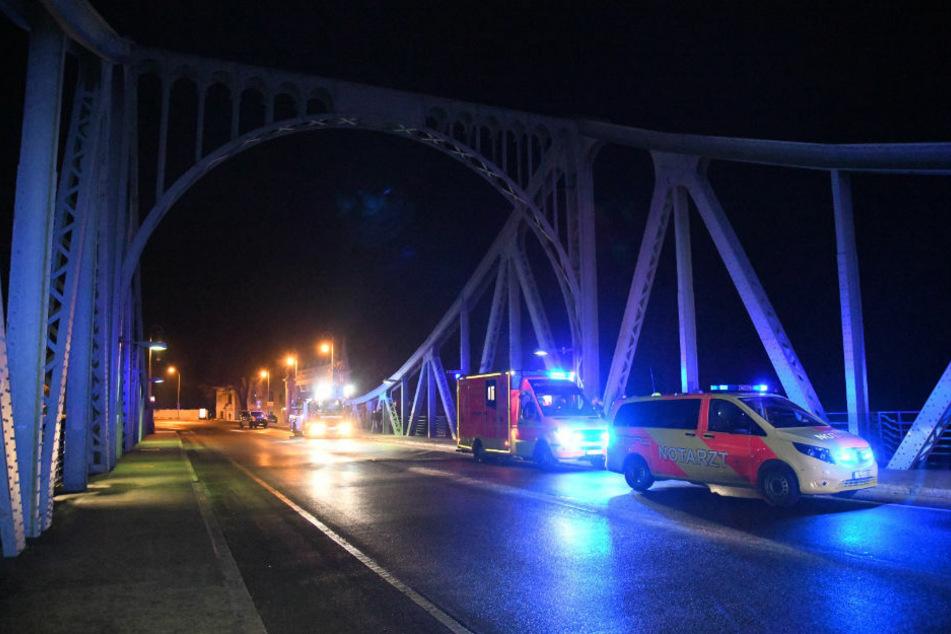 Rettungswagen stehen mit eingeschaltetem Blaulicht auf der Glienicker Brücke, unter der am Sonntagabend eine 59-Jährige hilflos in der eiskalten Havel trieb.