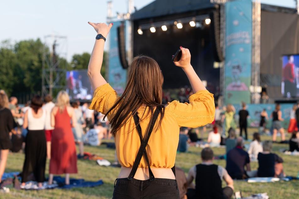 """Eine Frau tanzt während eines Konzerts der Band Meute, die in der Reihe """"Picknick-Konzerte"""" auf dem Messegelände auftritt. Die Maskenpflicht im Freien fällt in Zukunft weg."""